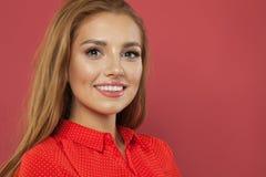 Stående av den unga nätta kvinnan som ler och ser kameran på rosa bakgrund med kopieringsutrymme fotografering för bildbyråer