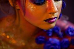 Stående av den unga och attraktiva kvinnan med konstmakeup Brännheta färger, blänker på framsida och blom- garnering Arkivbild