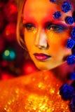 Stående av den unga och attraktiva kvinnan med konstmakeup Brännheta färger, blänker på framsida och blom- garnering Arkivfoton