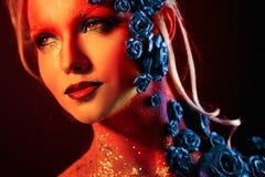 Stående av den unga och attraktiva kvinnan med konstmakeup Brännheta färger, blänker på framsida och blom- garnering Arkivfoto