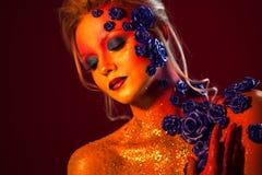 Stående av den unga och attraktiva kvinnan med konstmakeup Brännheta färger, blänker på framsida och blom- garnering Royaltyfri Bild
