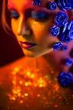 Stående av den unga och attraktiva kvinnan med konstmakeup Brännheta färger, blänker på framsida och blom- garnering Royaltyfria Foton