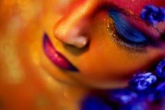 Stående av den unga och attraktiva kvinnan med konstmakeup Brännheta färger, blänker på framsida och blom- garnering Fotografering för Bildbyråer