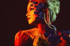 Stående av den unga och attraktiva kvinnan med konstmakeup Brännheta färger, blänker på framsida och blom- garnering Royaltyfria Bilder