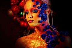 Stående av den unga och attraktiva kvinnan med konstmakeup Brännheta färger, blänker på framsida och blom- garnering Arkivbilder