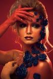 Stående av den unga och attraktiva kvinnan med konstmakeup Brännheta färger, blänker på framsida och blom- garnering Royaltyfri Foto