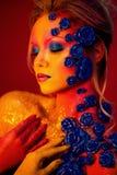 Stående av den unga och attraktiva kvinnan med konstmakeup Brännheta färger, blänker på framsida och blom- garnering Royaltyfri Fotografi