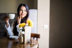 St?ende av den unga och n?tta kvinnan med koppen kaffe som ler i kaf? arkivfoton