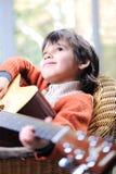 Stående av den unga pojken som leker den akustiska gitarren Royaltyfria Foton