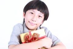 Stående av den unga pojken som rymmer en gåva Royaltyfria Foton