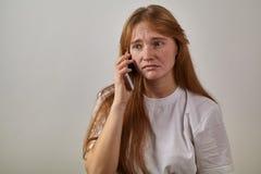 Stående av den unga röd-hövdade flickan med fräknar som rymmer telefonen fotografering för bildbyråer