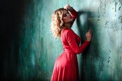 Stående av den unga sexiga blonda kvinnan i en röd klänning Arkivfoton