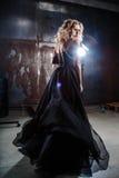 Stående av den unga sexiga blonda kvinnan i en svart klänning arkivfoto