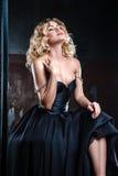Stående av den unga sexiga blonda kvinnan i en svart klänning Fotografering för Bildbyråer