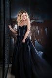 Stående av den unga sexiga blonda kvinnan i en svart klänning Royaltyfria Bilder