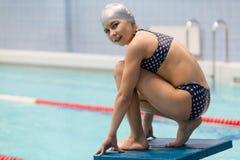 Stående av den unga simmaren som är klar att hoppa in i sportsimbassäng sportig flicka arkivfoton