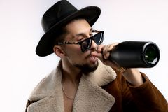 St?ende av den unga sk?ggiga mannen i svart hatt och brunt lag i svart solglas?gon som dricker fr?n en isolerad svart flaska fotografering för bildbyråer