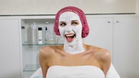Stående av den unga slanka kvinnliga klienten i skönhetklinik Blinka och le på kameran Kosmetologkontor i modernt lager videofilmer