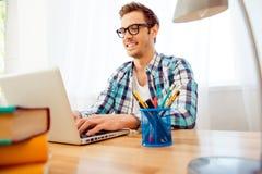 Stående av den unga smarta affärsmannen i exponeringsglas som skriver på bärbara datorn Arkivbild