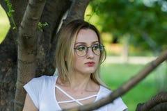 Stående av den unga smartlkvinnan i glasögon till och med trädfilialen i parkera Royaltyfri Bild