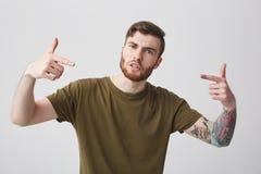Stående av den unga snygga negativa aggressiva skäggiga tatuerade mannen med kort hår i tillfällig stilfull brun t-skjorta Arkivbilder
