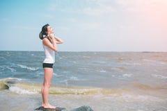 Stående av den unga sportiga kvinnan i hörlurar som kopplar av, medan sitta nära havet i sommar, attraktivt kvinnligt lyssna fotografering för bildbyråer