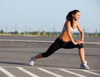 Stående av den unga sportiga kvinnan som gör sträcka övning. Athlet Arkivbilder