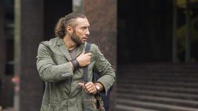 Stående av den unga stilfulla mannen med påsen i gatan Royaltyfri Foto