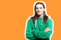 Stående av den unga stiliga mannen i den gröna hoodien som ser i den orange bakgrunden för kameraagains, konstcollage royaltyfri bild