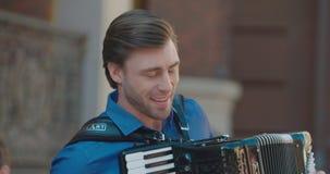 Stående av den unga stiliga mannen med det nätta leendet som spelar dragspelet på dörren Gatamusiker längd i fot räknat 4k stock video