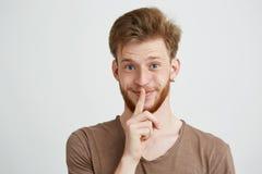 Stående av den unga stiliga mannen med skägget som ser kameran som ler visning för att hålla tystnad över vit bakgrund arkivfoto