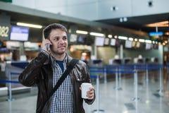 Stående av den unga stiliga mannen som går i den moderna flygplatsterminalen, talande smart telefon och att resa med påsen och ka Royaltyfria Foton