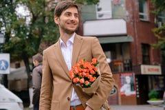 Stående av den unga stiliga mannen som ler rymma en grupp av rosor Royaltyfri Bild