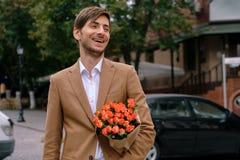 Stående av den unga stiliga mannen som ler rymma en grupp av rosor Royaltyfri Fotografi