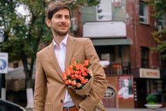 Stående av den unga stiliga mannen som ler rymma en grupp av rosor Fotografering för Bildbyråer