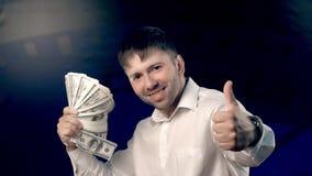 Stående av den unga stiliga mannen som rymmer mycket pengar i hans hand, vinkar dem och uttrycker fröjd arkivfilmer