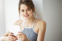 Stående av den unga tonårs- gladlynta flickan i hörlurar som ler se kameran som surfar rengöringsduk som bläddrar internet på min Royaltyfri Foto