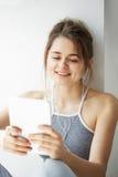 Stående av den unga tonårs- gladlynta flickan i hörlurar som ler se minnestavlan som surfar rengöringsduk som bläddrar internetsa Arkivbilder