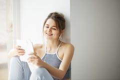 Stående av den unga tonårs- gladlynta flickan i hörlurar som ler se minnestavlan som surfar rengöringsduk som bläddrar internetsa Royaltyfri Fotografi