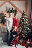 Stående av den unga vänliga familjen som ser kameran på julmorgon Fader, moder och dotter royaltyfri foto