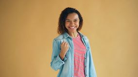 Stående av den upphetsade afrikansk amerikandamen som lyfter näven som firar framgånglycka stock video
