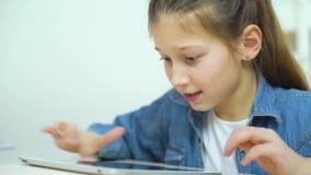 Stående av den upphetsade lilla flickan som spelar online spel på minnestavlan lager videofilmer
