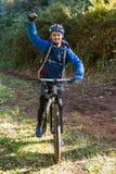 Stående av den upphetsade manliga bergcyklisten i skogen Arkivfoto