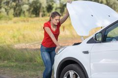 Stående av den upprivna kvinnan för barn som ser under huven av den brutna bilen Arkivfoton