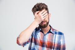 Stående av den upprivna mannen som täcker hans framsida med handen Arkivfoto