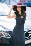 Stående av den ursnygga eleganta brunettkvinnan i en near svart bil för hatt Arkivfoto