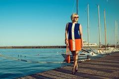 Stående av den ursnygga medelåldersa blonda kvinnan i moderiktig klänning och solglasögon som promenerar pir som rymmer en orange arkivfoto
