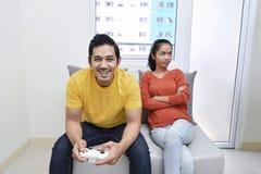 Stående av den uttråkade asiatiska kvinnan medan hennes pojkvän som spelar videoen Royaltyfria Bilder