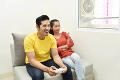 Stående av den uttråkade asiatiska kvinnan medan hennes pojkvän som spelar videoen Royaltyfria Foton