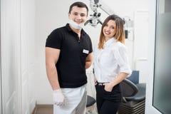 Stående av den vänliga manliga tandläkaren med den lyckliga kvinnliga patienten i modern tand- klinik dentistry arkivbild